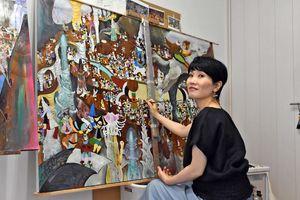 多くのキャラクターが登場する幻想的な世界を描く仁戸田典子さん=大分市