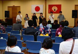 佐賀大学のボランティアグループによるアカペラを楽しむ本庄地区の住民ら=佐賀市の本庄公民館