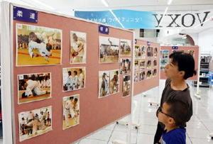 中学総体の熱戦を写した写真に見入る来店者=佐賀市新栄西のネッツトヨタ佐賀本店