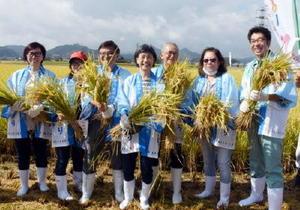 刈った稲を手に、小松政武雄市長(右)と記念写真を撮るシンガポールからの観光客=武雄市橘町