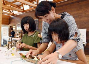 真剣な表情で工作に取り組む参加者たち=神埼市神埼町の「てるてるの森」情報館