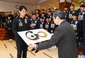 佐賀新聞社を表敬訪問し、中尾清一郎社長に今年のスローガンの記念パネルを贈るサガン鳥栖の金明輝監督(左)=佐賀市