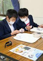 互いに見比べながらまが玉を作る若基小の児童=吉野ケ里歴史公園