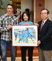 月間MVPに選ばれたトーレス選手に記念パネルを贈る日野利佳さん(中央)と中尾清一郎社長=佐賀新聞社