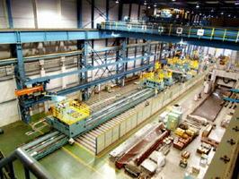 全長60メートル、完成した「深孔ぐり加工機」(中央)。大型トレーラー十数台に分包して納入した=唐津市二タ子、唐津プレシジョン工場内