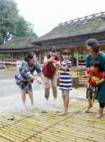 竹を並べた「やな」と呼ばれる仕掛けに落ちてきたアユを捕まえる家族連れ=熊本県甲佐町のやな場