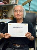 「サラバイメダル」の賞状を手にする新井康平特任教授=佐賀市の佐賀大本庄キャンパス