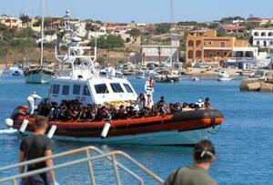 9日、イタリア最南端の島ランペドゥーザに到着する難民を乗せたボート(ロイター=共同)