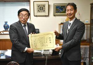 ヘルスケア産業づくり貢献大賞の特別賞の表彰状を受け取った吉村正社長(左)=佐賀市の大神