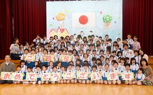 「ご即位おめでとうございます」とお祝いの言葉を声に出しながら記念撮影した三光幼稚園の園児たち=佐賀市の同園
