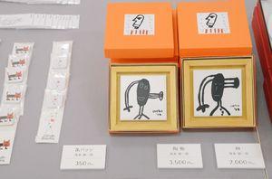 アーティストのグッズと作品が並ぶ会場=佐賀市中の小路の佐賀玉屋本館