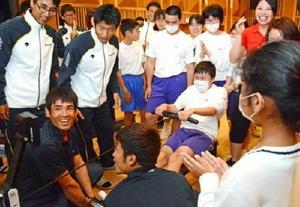トレーニング機器を使い1000㍍の「レース」に挑戦する子どもたちと応援する実業団の選手ら=佐賀市の富士公民館