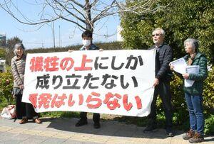 原発を反対する横断幕を掲げ、通行人に訴えるメンバーたち=佐賀市の神野東1丁目交差点付近