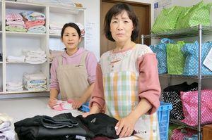 乾燥の終わった洗濯物を畳む中野美智子さん(右)