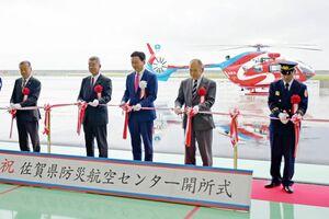 県防災航空センターの開所を記念してテープカットをする山口祥義知事(右から3人目)ら=佐賀市川副町