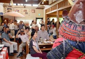 甲冑姿の写真を撮るツアー客ら=佐賀市松原の肥前通仙亭