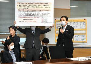 新型コロナウイルスの対策本部会議の冒頭、飲食店への時短要請を5月末まで延長すると表明した山口祥義知事(右)=20日、佐賀県庁