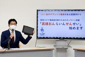 小中学生に貸与しているタブレット端末を手に、オンライン授業の試行について記者会見をする小松政武雄市長=市役所