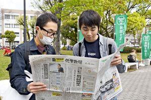 配られた新聞を見る学生=佐賀市の佐賀大学本庄キャンパス