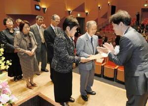 壇上に並んで結婚50年の表彰を受ける金婚さん夫婦。右は富吉賢太郎佐賀新聞社専務取締役=唐津市高齢者ふれあい会館りふれ