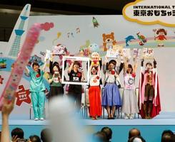 「東京おもちゃショー2019」のオープニングセレモニーで玩具を掲げる各企業の担当者=13日午前、東京都江東区の東京ビッグサイト
