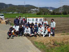 畑や耕作放棄地を「和桑農園」と名付けて、整備し、桑の苗を植え付けた参加者ら=神埼市神埼町の尾崎東分地区(神埼市提供)