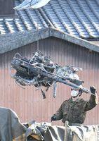 墜落現場から回収されるAH64D戦闘ヘリコプターに搭載されていた30ミリ機関砲=8日午後3時35分、神埼市千代田町