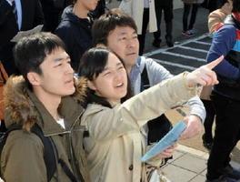 合格発表で自身の受験番号を見つけ、喜ぶ受験生(中央)と家族=佐賀市の佐賀大学本庄キャンパス