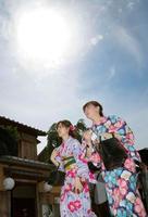 強い日差しの下、京都市内を歩く着物姿の女性=26日午後
