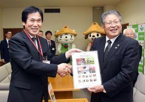 オリジナルフレーム切手を笑顔で受け取る松本茂幸市長(右)。左は日本郵便九州支社経営管理本部総務・人事部専門役の立石仁司さん=神埼市役所
