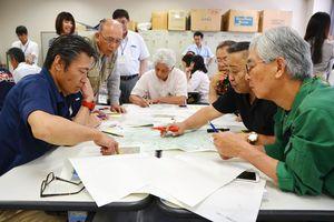 地図や気象データを囲み、避難指示などについて話し合う参加者たち=佐賀市のほほえみ館
