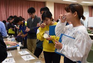 きき酒に挑戦する学生たち=佐賀市の佐賀大学「菱の実会館」