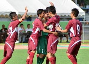 サッカー決勝・西有田-昭栄 PK戦の末に勝利し、GK森山(中央)のもとに駆け寄って喜ぶ西有田の選手たち=鳥栖市陸上競技場
