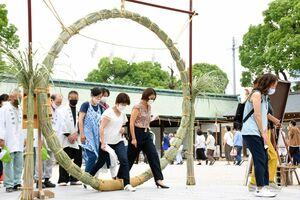 無病息災を願い、茅の輪をくぐる参拝者=佐賀市松原の佐嘉神社