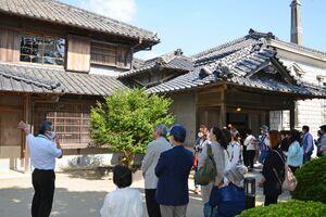 旧高取邸を前に施設職員(左)の説明を受けるツアー参加者たち=唐津市北城内