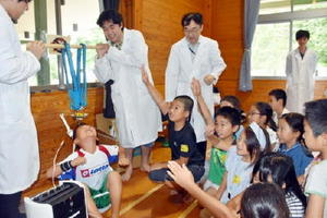 磁力を使って児童を持ち上げる実験に参加する子どもたち=佐賀市の中央児童センター