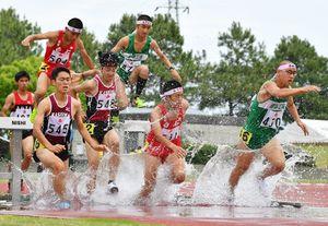 陸上男子3000メートル障害で水しぶきを上げながら障害を越える選手たち=鹿島市陸上競技場