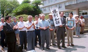 「勝利和解」の垂れ幕を掲げ、和解を喜ぶ原告団=平成13年7月10日、佐賀地裁