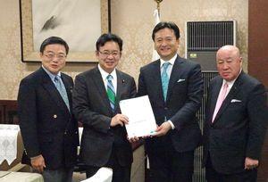 上野健一郎財務副大臣(左から2人目)に予算確保に向けた提案書を手渡す山口祥義知事=東京・霞が関の財務省