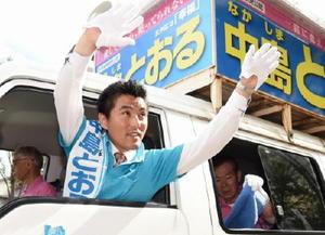 選挙カーから大きく手を振って支持を訴える中島徹候補=佐賀市のエスプラッツ前
