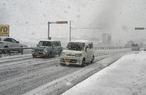 雪が積もった平野部の幹線道路。日中も時折、激しく降り、「スリップ注意」の電光表示も=10日午前9時6分、杵島郡江北町