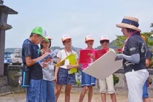 尾﨑葉子館長から町の歴史などを学ぶ有田まちなか案内ジュニア隊のメンバー=有田町の陶山神社