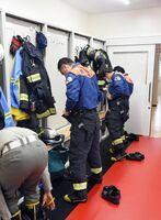 訓練のため、新設された出動準備室で防火服に着替える署員たち=唐津市鎮西町の唐津市消防署北部分署