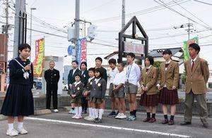 新たに設置された電光掲示板の前であいさつする神埼中の高木瑚桃さん(左)=神埼市の神埼署
