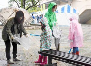 雨の中、ごみを拾う参加者=佐賀市の県立森林公園