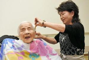 髪をカットする佐賀市支部員の新郷幸子さん(右)=佐賀市のロザリオの園