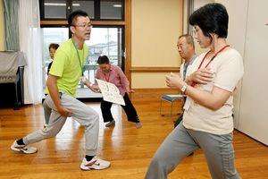 ミズのスタッフ(左)からロコモティブシンドローム予防の運動指導を受ける参加者ら=佐賀市の本庄公民館
