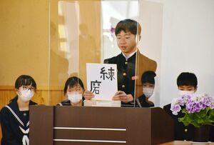 決意を記した色紙を掲げ、将来の夢や目標を発表する生徒=多久市の東原庠舎中央校
