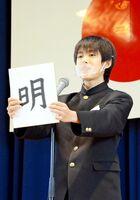 一文字を書いた色紙を掲げ、誓いの言葉を述べる生徒=有田町の有田中