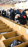 入札手板を手にしながらノリの品質をチェックする買い付け業者=佐賀市の佐賀海苔共販センター